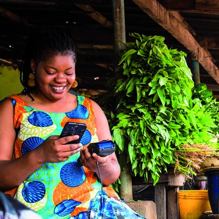 Dame au marché avec outils digitaux pour la tontine